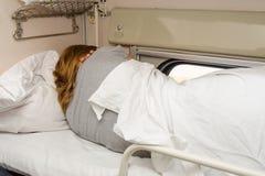 La muchacha duerme en el estante superior de los asientos laterales en el carro de segunda clase dado vuelta a la pared Imagen de archivo