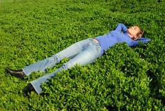 La muchacha duerme en una hierba Fotos de archivo libres de regalías