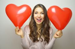 La muchacha dulce con el corazón de la tarjeta del día de San Valentín hincha mirando la cámara Mujer joven preciosa con dos glob Foto de archivo libre de regalías