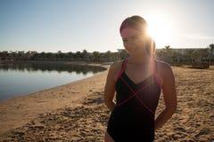 La muchacha dulce, delgada se opone en la playa a la puesta del sol Los rayos del sol brillan en la cámara Fotografía de archivo libre de regalías