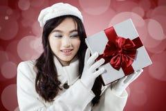 La muchacha dulce en ropa del invierno consigue un presente Imagen de archivo libre de regalías