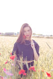 La muchacha dulce hermosa con los labios grandes plump con la amapola a disposición que camina en un campo en un día soleado en l Imágenes de archivo libres de regalías