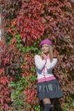 La muchacha dulce hermosa en una boina y una falda camina entre el color rojo brillante de hojas en día soleado brillante del par Imágenes de archivo libres de regalías