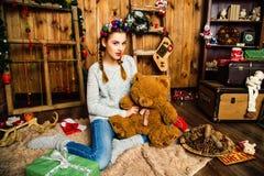 La muchacha dulce se sienta con un peluche refiere el fondo de la Navidad Imagen de archivo libre de regalías