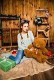 La muchacha dulce se sienta con un peluche refiere el fondo de la Navidad Imagen de archivo