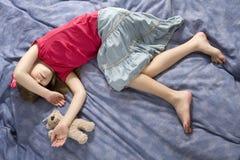 la muchacha durmiente en arqueamiento con peluche-lleva Fotografía de archivo libre de regalías