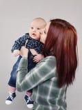 La muchacha el adolescente besa al bebé Imagenes de archivo