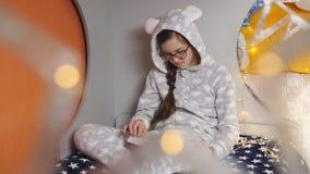 La muchacha el adolescente lee el libro que se sienta en la cama en pijamas calientes almacen de metraje de vídeo