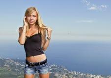 La muchacha el blonde contra el cielo azul Imagen de archivo libre de regalías