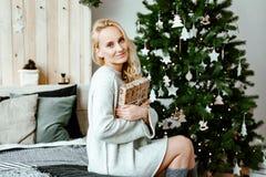 La muchacha el blonde en un suéter acogedor ligero abre los regalos de la Navidad Imágenes de archivo libres de regalías