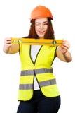 La muchacha el constructor con el nivel del agua en manos  Foto de archivo libre de regalías