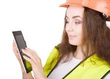 La muchacha el constructor en un casco y un chaleco con una tableta electrónica   Foto de archivo