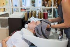 La muchacha el peluquero se lava el pelo después de cortar al individuo joven, hermoso en el salón de belleza Fotos de archivo libres de regalías