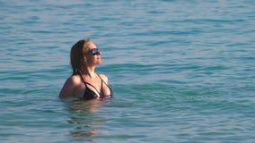La muchacha el rubio en un bañador negro y vidrios negros El modelo hermoso con el cuerpo se está divirtiendo en cristal almacen de video