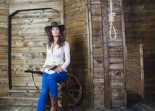 La muchacha el vaquero con un arma y un arma Fotografía de archivo libre de regalías