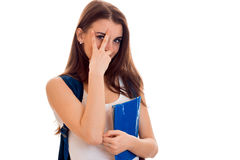 La muchacha elegante alegre del estudiante en deporte marrón viste con la mochila en sus hombros y la carpeta para los cuadernos  Imagen de archivo