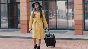 La muchacha elegante con el pelo largo en un sombrero y vidrios viene con equipaje almacen de video