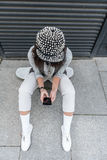 La muchacha elegante del adolescente está utilizando el teléfono Fotos de archivo libres de regalías