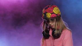 La muchacha elegante del adolescente juega música en la tabla de DJ, fondo ahumado almacen de video