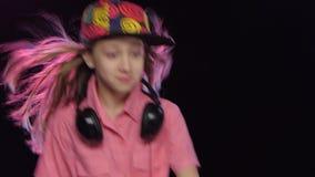 La muchacha elegante del adolescente juega música y baila en la tabla de DJ metrajes