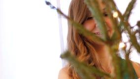 La muchacha elegante del cierre de la cámara lenta adorna el árbol de navidad almacen de video