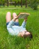 La muchacha elegante del estudiante se relaja con el libro en parque hermoso del verano en el día soleado Imagen al aire libre de Fotos de archivo libres de regalías