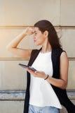 La muchacha elegante del inconformista está utilizando la tableta digital para la navegación en el ambiente urbano Imagen de archivo