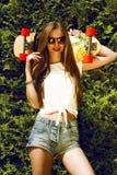La muchacha elegante en gafas de sol presenta con longboard adentro foto de archivo