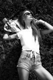 La muchacha elegante en gafas de sol presenta con longboard de imágenes de archivo libres de regalías
