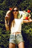 La muchacha elegante en gafas de sol presenta con longboard de imagenes de archivo