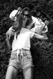 La muchacha elegante en gafas de sol presenta con longboard de fotografía de archivo libre de regalías