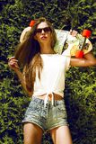La muchacha elegante en gafas de sol presenta con longboard de fotos de archivo libres de regalías