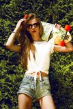 La muchacha elegante en gafas de sol presenta con longboard de imagen de archivo
