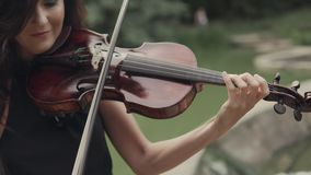 La muchacha elegante en vestido toca el violín al aire libre Violinista elegante en bosque almacen de video