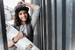 La muchacha elegante feliz está riendo mientras que se inclina en la cerca Imagen de archivo libre de regalías