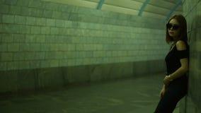 La muchacha elegante hermosa en vidrios se coloca en un paso inferior peatonal cerca de la pared metrajes