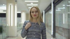 La muchacha elegante joven en vestido camina con en el centro comercial grande almacen de video