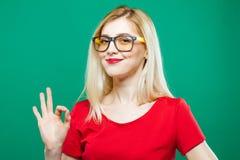 La muchacha elegante linda en lentes está mostrando la muestra aceptable en fondo verde Blonde hermoso con el pelo largo y el top Foto de archivo