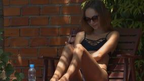 La muchacha elegante mancha el estómago con la protección solar en sombra