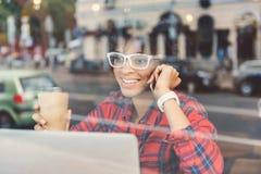 La muchacha elegante positiva está llamando por smartphone Imágenes de archivo libres de regalías