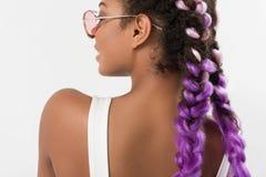 La muchacha elegante positiva está mostrando su peinado moderno Foto de archivo