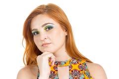 La muchacha elegante reflexiona sobre un tema Color que lleva de la muchacha Redheaded Fotografía de archivo