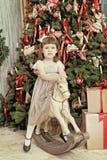 La muchacha elegante se sienta en un caballo del juguete cerca Fotografía de archivo