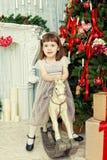 La muchacha elegante se sienta en una mecedora del caballo Imagen de archivo libre de regalías
