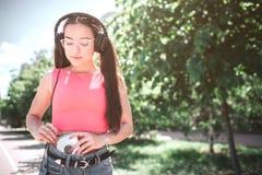 La muchacha elegante y hermosa que le gusta escuchar la música está mirando abajo el jugador Ella conecting los auriculares con Imágenes de archivo libres de regalías