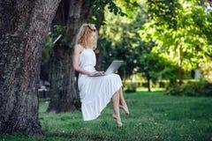 La muchacha eleva y mantiene flotando con el ordenador portátil fotografía de archivo libre de regalías