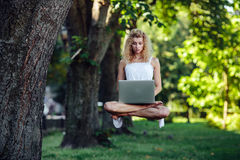 La muchacha eleva y mantiene flotando con el ordenador portátil fotografía de archivo
