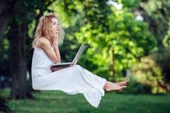 La muchacha eleva y mantiene flotando con el ordenador portátil imagen de archivo libre de regalías