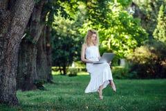 La muchacha eleva y mantiene flotando con el ordenador portátil fotos de archivo