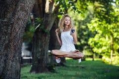 La muchacha eleva y mantiene flotando en naturaleza fotografía de archivo libre de regalías